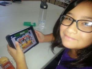 "A latinia enjoys playing a video game at ""Latinitas Summer Camp 2015"""