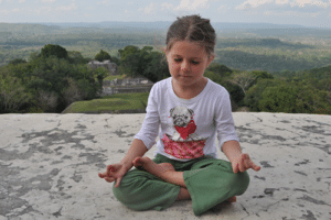 A tween girl meditating in Belize. Phot by: harmoniouskids.com